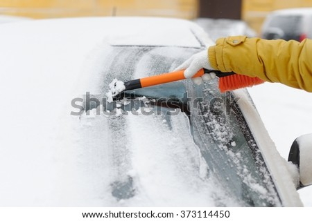 A woman in winter removes snow with the car - stock photo