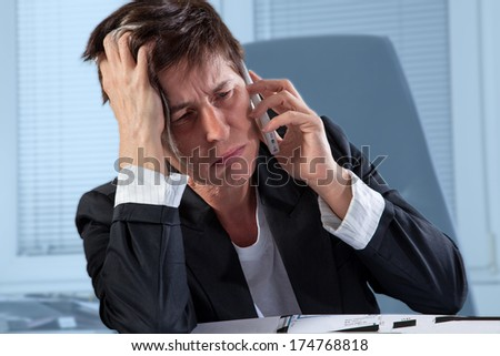 A woman is a step before to break out in tears during a phone call in her office. - stock photo