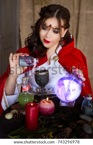A woman is a witch, a sorceress who hides ingredients in a cup, gives a magic drink, bewitch. A table with a crystal ball.