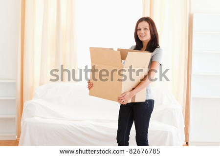 A woman is carrying a cardboard - stock photo