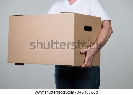A woman is carrying a heavy cardboard isolated on a grey background.