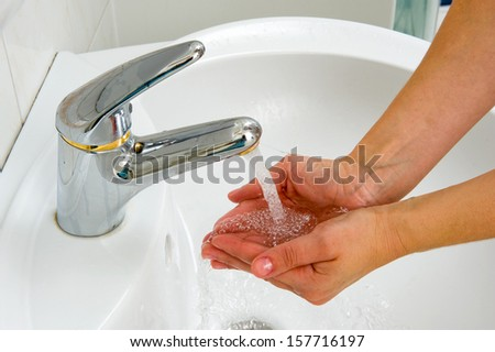 A woman is catching water from a tap in her hands