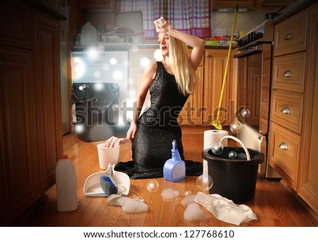 A woman is cleaning the floor acting as a glamorous movie star in an elegant dress for a career or housework concept. - stock photo