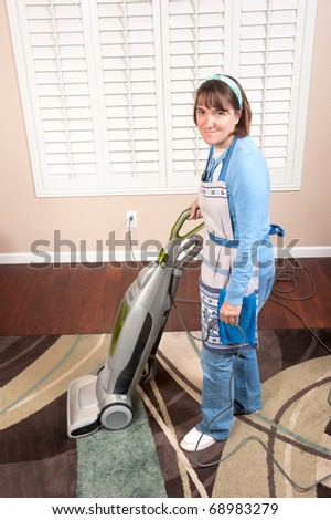 A woman is conducting housework by vacuuming a rug on a wooden floor.