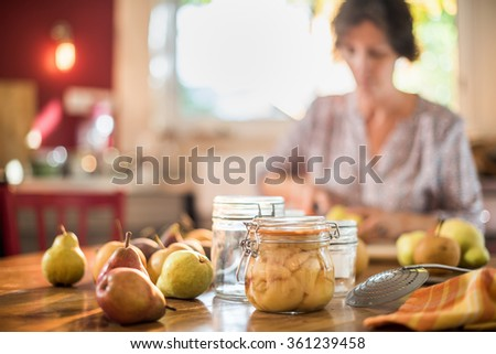 A woman is cutting pears in a kitchen, sitting at a wooden table in order to make rustic and old fashioned jar of homemade canned fruits. Focus on the jar with pears around. Blur background - stock photo