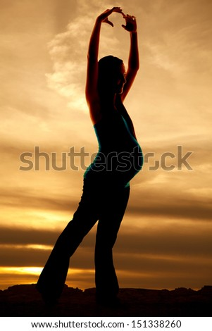 a woman is dancing pregnant silhouette in the sunset.