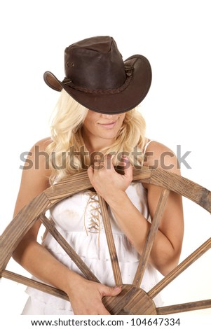 A woman is dressed as a cowgirl by a wagon wheel. - stock photo