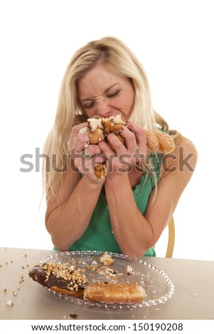 A woman is eating a lot of doughnuts really fast. - stock photo
