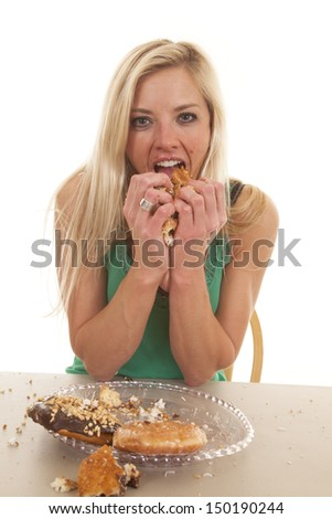 A woman is eating a plate full of donuts.