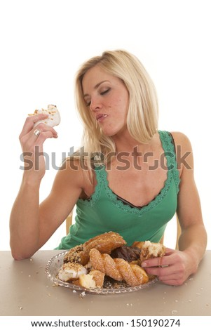 A woman is eating doughnuts and loving them.