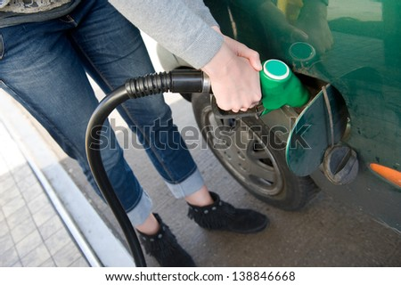 A woman is filling her car with fuel at a filling station - stock photo
