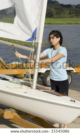 A woman is fixing the sail on her sailboat.  She is looking away from the camera.  Vertically framed shot. - stock photo