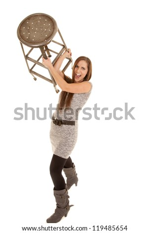 a woman is frustrated with school or work and ready to throw the stool - stock photo