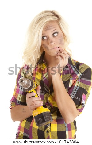A woman is holding a drill with a puzzled look on her face. - stock photo