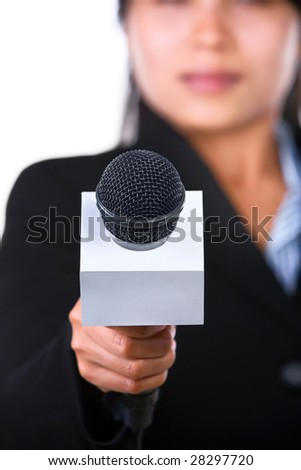 A woman is holding a microphone to the camera. Shot against white background. - stock photo