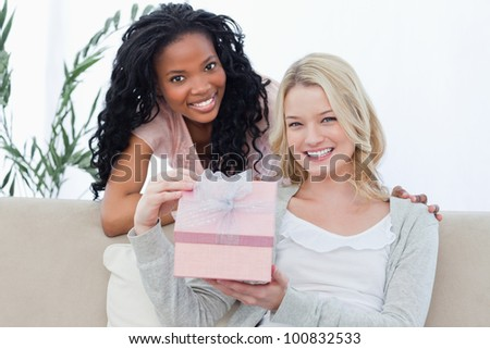 A woman is holding a present and smiling at the camera at the camera with her friend