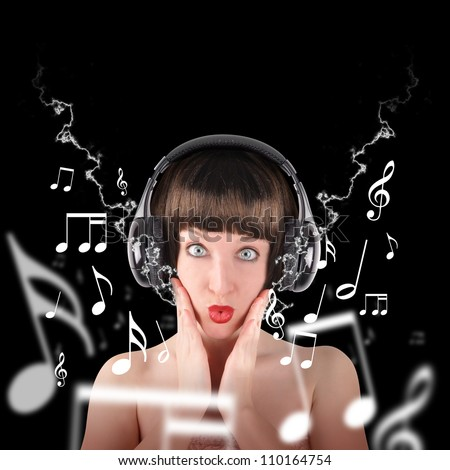 A woman is holding earphones listening to music on a black background. There are music notes in the background. - stock photo