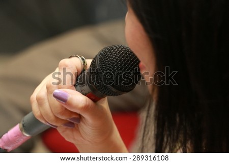 a woman is holding microphone in her hand