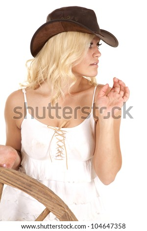 A woman is holding onto a wagon wheel and looking to the side. - stock photo