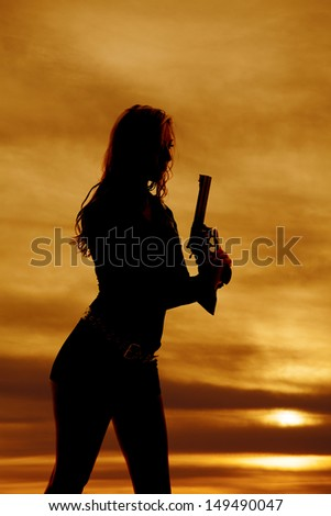 A woman is holding up a gun in the sunset silhouetted.