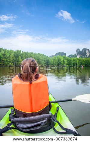 a woman is kayaking in mangrove forest at Krabi, Thailand. Mangrove forest, Beautiful blue sky Intertidal forest. important for ecology coast and co-operation community. Background.Adventure - stock photo