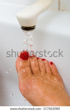 A woman is keeping her foot under the hot warm water of a bath faucet - stock photo