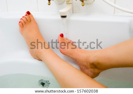 A woman is keeping her foot under the hot water of a bath faucet