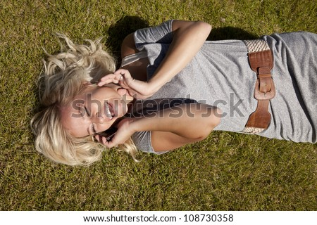 A woman is laying on the grass laughing and talking on her phone. - stock photo