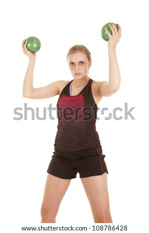 A woman is lifting two medicine balls above her head. - stock photo