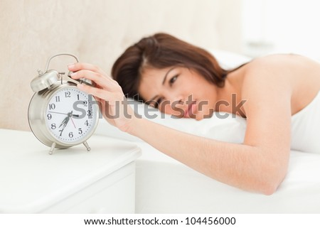 A woman is lying on the bed awake with her hand on the alarm clock, showing the time. - stock photo