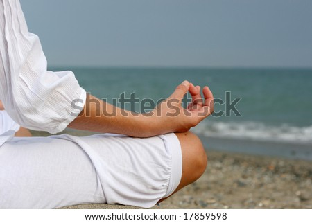 A woman is meditating by the sea