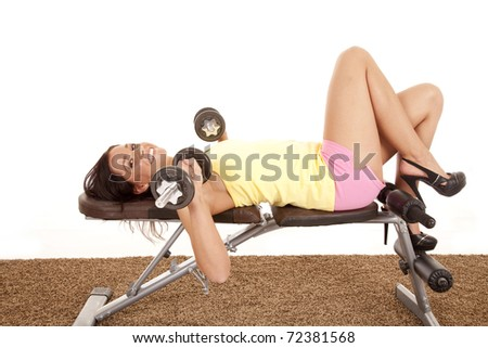 A woman is on a workout bench with some weights smiling. - stock photo