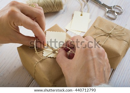 A woman is preparing gifts and writing labels for Christmas - stock photo