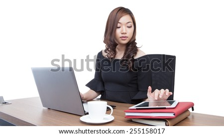 A woman is reading the business news on a digital tablet. She is sitting at a wooden desk. Businesswoman wearing casual sitting at desk and looking latest business news on digital tablet in the office