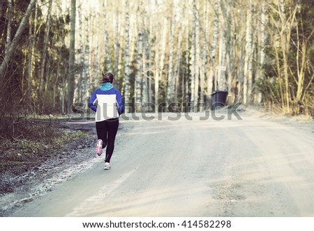A woman is running on an empty street. She is enjoying the silence and feeling of exercising. Image has a vintage effect applied. - stock photo