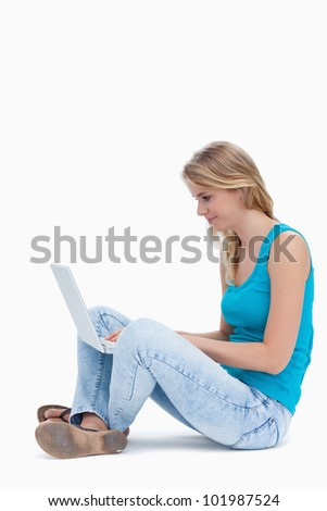 A woman is sitting down on the ground typing on a laptop against a white background