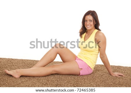 A woman is sitting in a yellow tank top and pink shorts. - stock photo