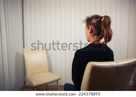 A woman is sitting on a chair and is waiting to see her doctor or therapist