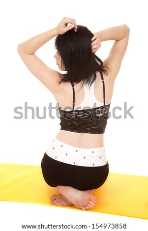 A woman is sitting on a mat with her back facing forward. - stock photo