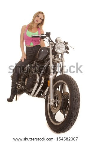 A woman is sitting on a motorcycle with a serious expression.