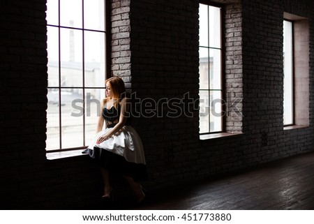 A woman is sitting on the window sill and looking away and thinking