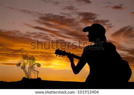 A woman is sitting with a guitar in the sunset by a camp fire. - stock photo