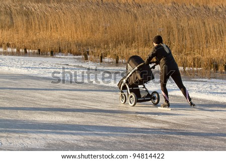A woman is skating with a children's buggy on the famous dutch Bonkevaart (Friese Elfstedentocht) - stock photo