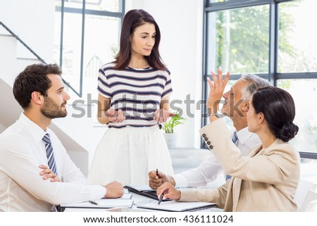 A woman is standing and looking at her colleagues at work - stock photo