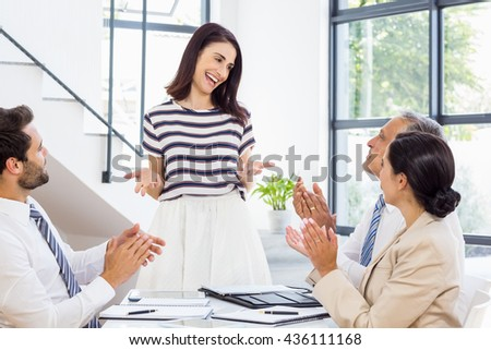 A woman is standing, smiling and talking to her colleagues who are sitting at work - stock photo