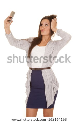 A woman is taking a picture of herself with her cell phone. - stock photo