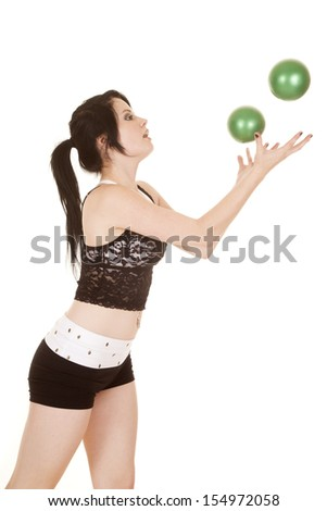 A woman is throwing green balls up in the air.