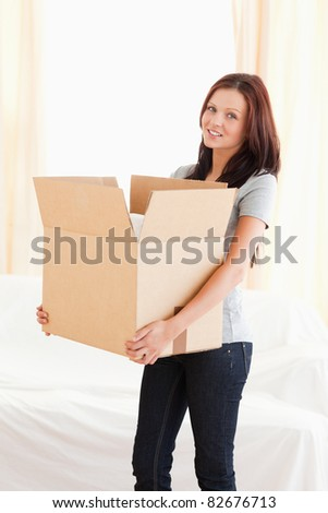 A woman is transporting a filled cardboard