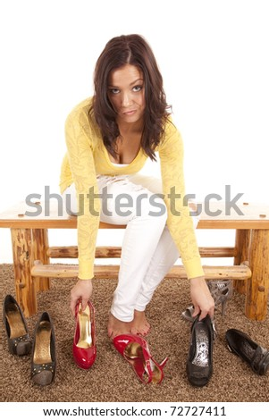 A woman is trying to decide which shoes to wear. - stock photo