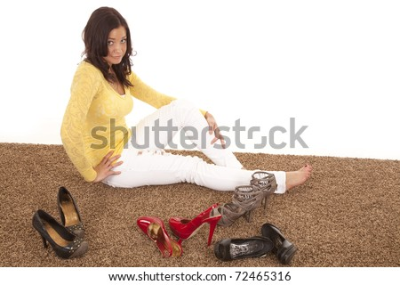 A woman is tying to decide which shoes she wants to wear. - stock photo